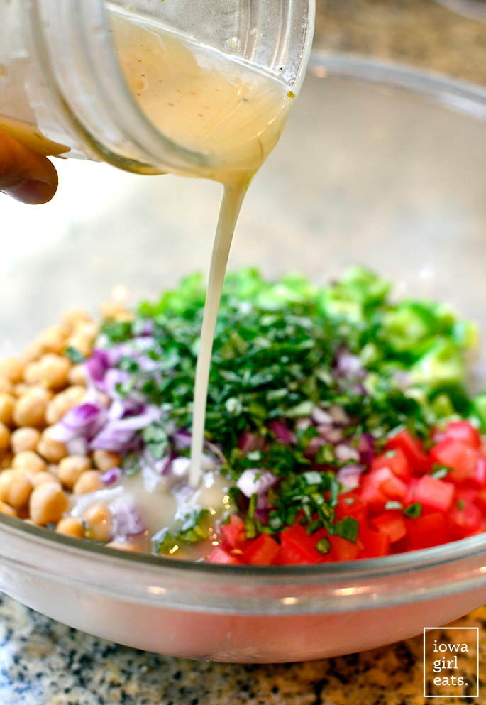 dressing being poured onto italian chickpea salad