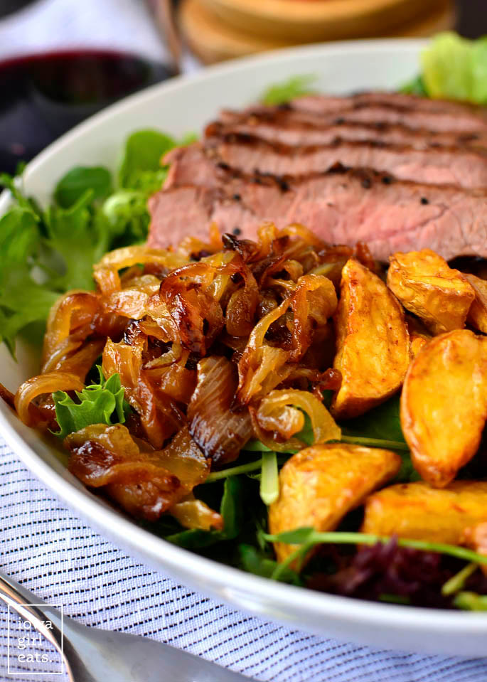 caramelized onions and potatoes on a steak salad