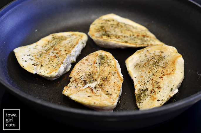 Skillet of chicken cutlets cooking.