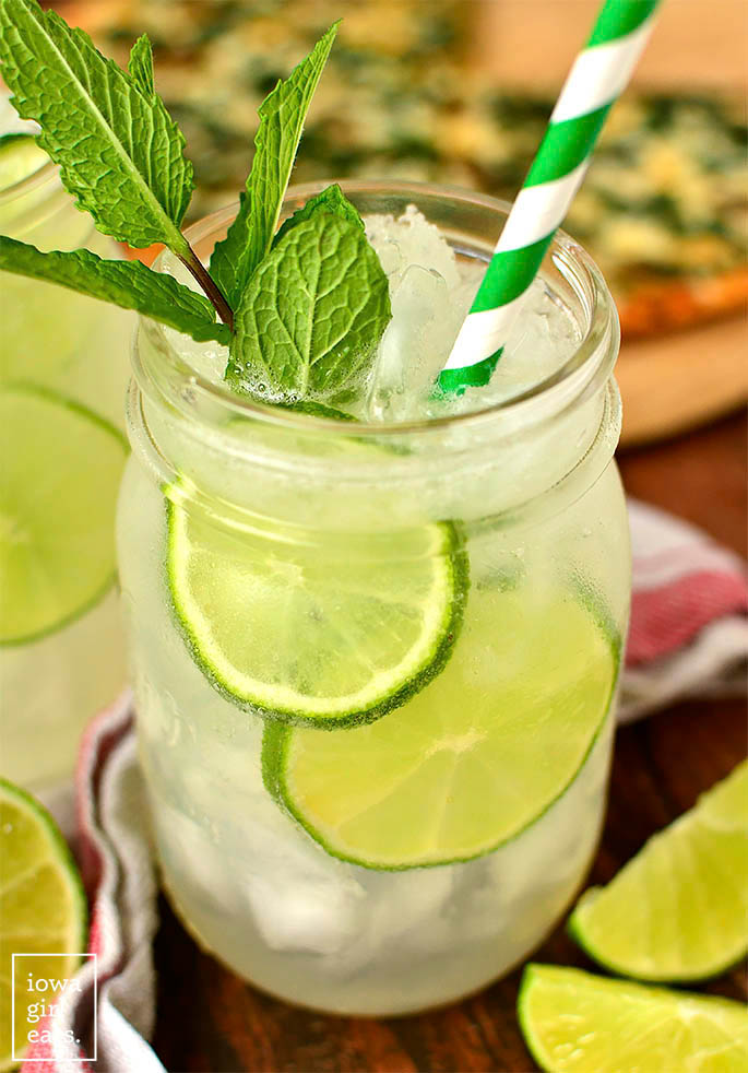 sparkling mint limeade in a glass with lime slices and a straw