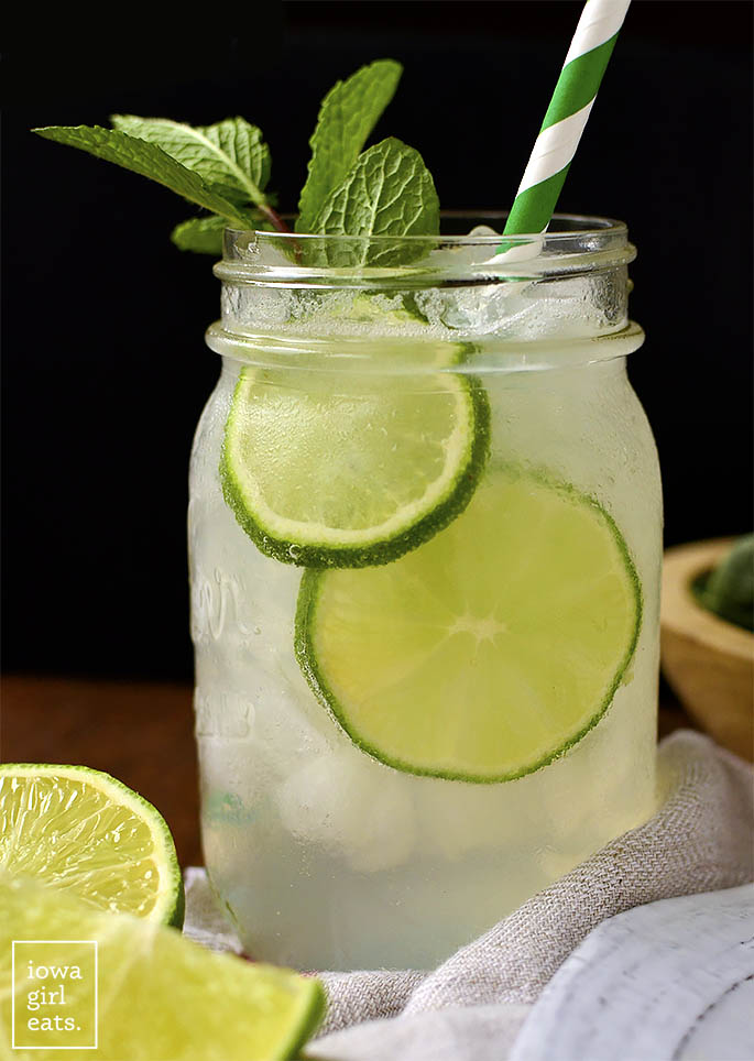 Glass of Sparkling Mint Limeade with mint, limes, and a straw.