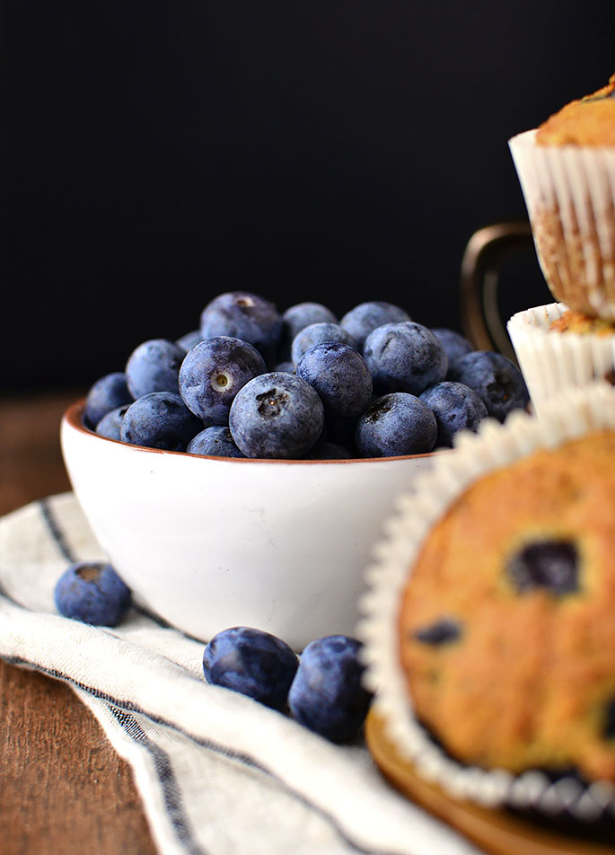 Bowl of blueberries with muffins on the side