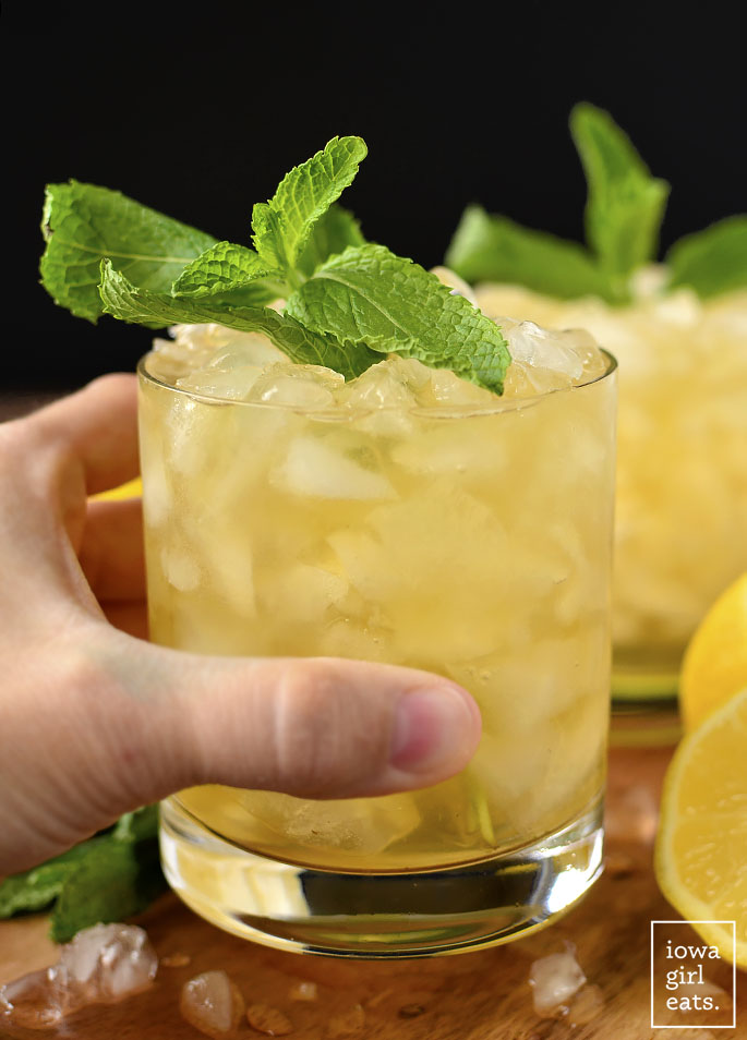 Hand holding a glass of Lemon-Ginger Mint Juleps | iowagirleats.com