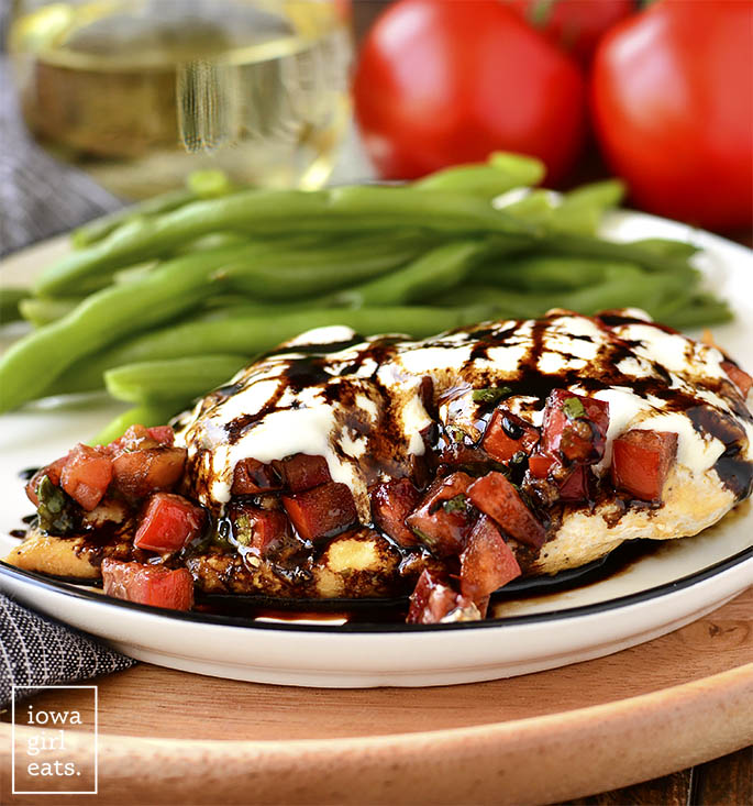 Photo of Mozzarella Bruschetta Chicken and green beans on a plate with a glass of wine. | iowagirleats.com