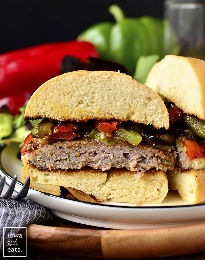 Italian Sausage and Peppers Cheeseburger sliced in half on a plate.