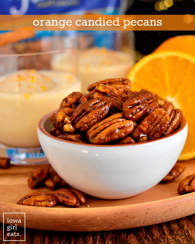 Bowl of Orange Candied Pecans with Spiked Eggnog glasses in the background