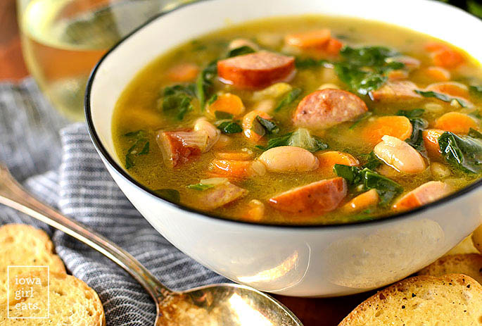 Bowl of soup with beans, sausage, and spinach