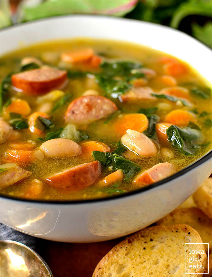 hearty soup with sausage, white beans, and spinach in a bowl