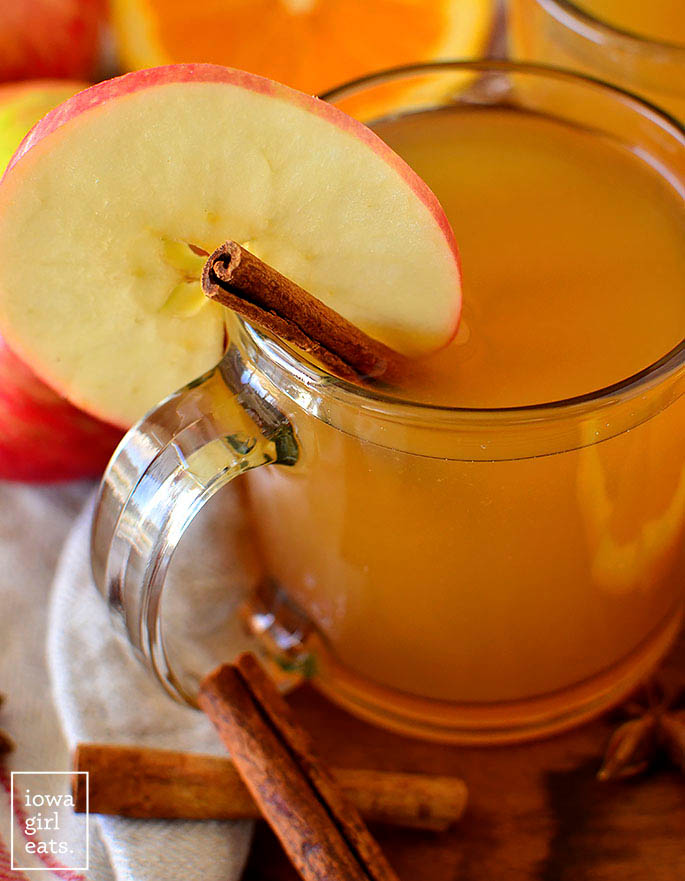 Mulled apple cider in a glass with cinnamon and an apple slice