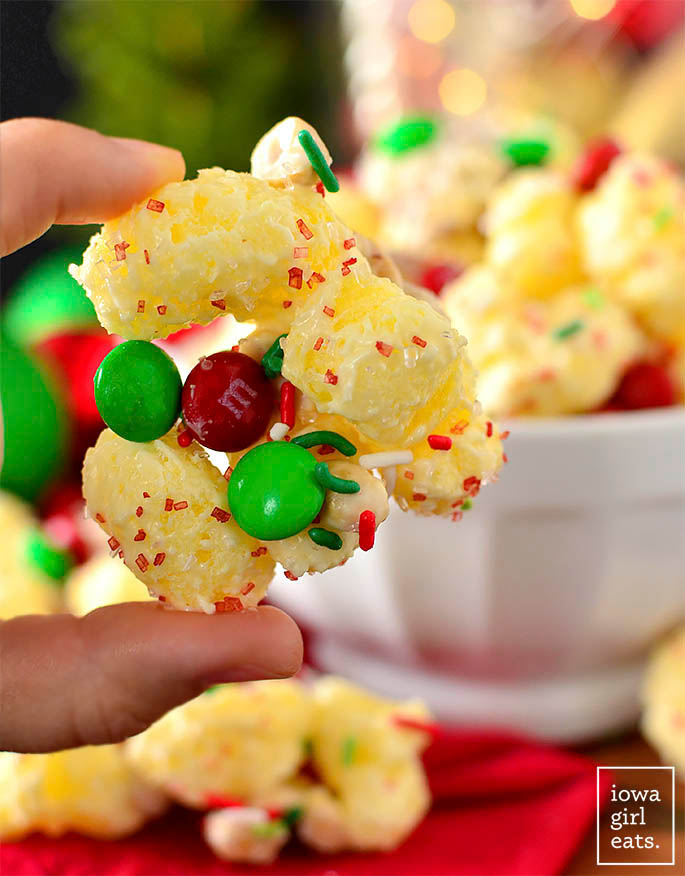 Hand holding a hunk of white chocolate puffcorn holiday mix